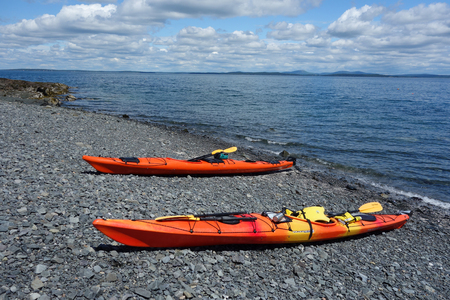 BAR HARBOR, MAINE - JULY 4, 2017: Sea kayaks on a rocky beach in Bar Harbor. Bar Harbor is a famous summer colony in the Down East region of Maine Editorial