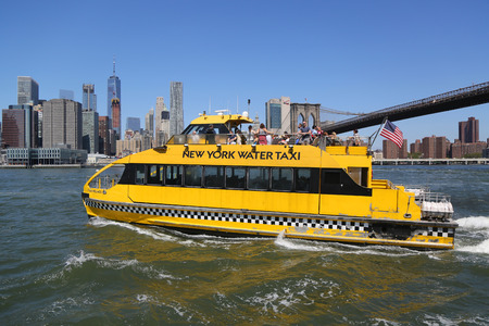 NEW YORK - AUGUST 13, 2017: New York City Water Taxi under Brooklyn Bridge. NYC Water Taxi offering commuter and sightseeing service along the East River and Hudson River