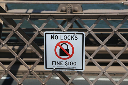 BROOKLYN, NEW YORK - AUGUST 13, 2017: Sign on the Brooklyn Bridge warning people of a $100 fine if you place a lock on the bridge Editorial