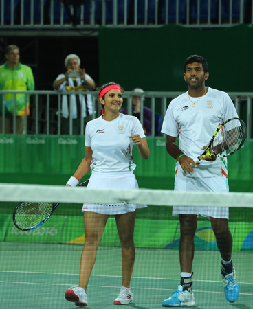 RIO DE JANEIRO, BRAZIL - AUGUST 12, 2016: Mixed doubles team India Sania Mirza (L)and Rohan Bopanna celebrate victory after quarterfinal of the Rio 2016 Olympic Games at the Olympic Tennis Centre