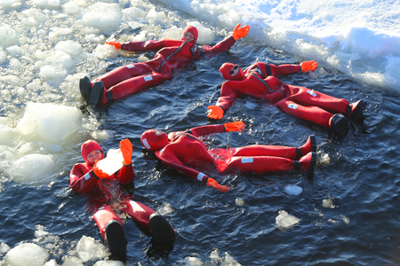 KEMI, FINLAND - FEBRUARY 18, 2017: Unidentified tourists geared up with a survival suit ice swim in frozen Baltic Sea 報道画像