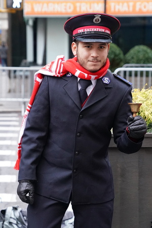 NEW YORK - DECEMBER 19, 2017: Salvation Army soldier performs for collections in midtown Manhattan. This Christian organization is known for its charity work, operating in 126 countries