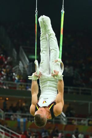 RIO DE JANEIRO, BRAZILIË - AUGUSTUS 15, 2016: Artistieke turner Dennis Goossens van België concurreert bij de finale van de herenringen op artistieke gymnastiekcompetitie bij Olympische Spelen Rio 2016 Redactioneel