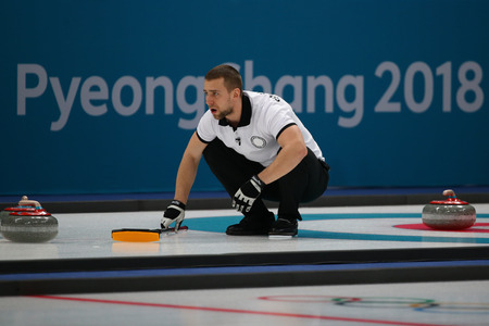 GANGNEUNG, SOUTH KOREA - FEBRUARY 10, 2018: Aleksandr Krushelnitskii of Olympic Athlete from Russia competes in the Mixed Doubles Round Robin curling match at the 2018 Winter Olympics