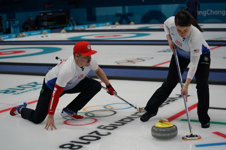 GANGNEUNG, SOUTH KOREA - FEBRUARY 10, 2018: United States siblings Matt (R), and Becca Hamilton sweep the ice during a mixed doubles curling match against Chinas Wang Rui and Ba Dexin at the 2018 Winter Olympics