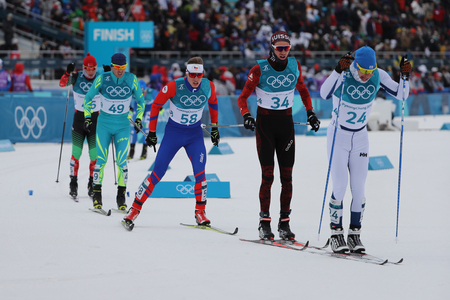 PYEONGCHANG, SOUTH KOREA - FEBRUARY 11, 2018: Skiers compete at mass start in the Mens 15km + 15km Skiathlon at the 2018 Winter Olympic Games at Alpensia Cross-Country Skiing Centre