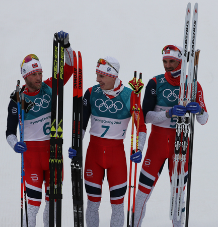 PYEONGCHANG, SOUTH KOREA - FEBRUARY 11, 2018: M J Sundby (L),  S H Krueger and H C Holund all of Norway celebrate victory at  mass start in the Mens 15km + 15km Skiathlon at the 2018 Winter Olympics