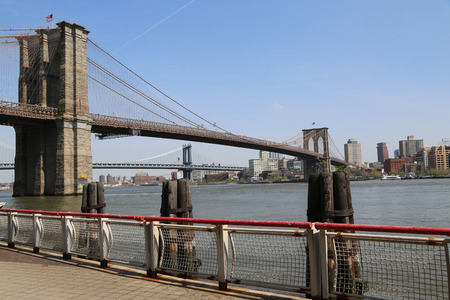 NEW YORK - MAY 3, 2018: Famous Brooklyn Bridge view from South Street Seaport. The Brooklyn Bridge is the one of the oldest suspension bridges in the USA was completed in 1883 Sajtókép