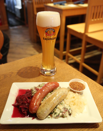 NEW YORK - MAY 3, 2018: A glass of German wheat beer Erdinger hefeweizen and sausage plate served in New Yorks restaurant Editorial