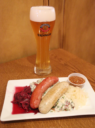 NEW YORK - MAY 3, 2018: A glass of German wheat beer Erdinger hefeweizen and sausage plate served in New York's restaurant