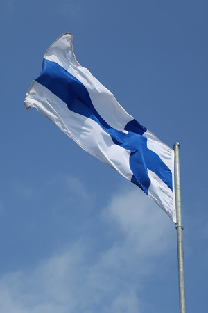 Flag of Finland waving in the wind against blue sky