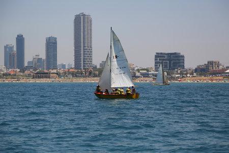 TEL AVIV, ISRAEL - APRIL 29, 2017: Yacht in Mediterranean Sea and Tel Aviv beachfront