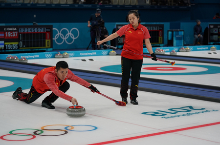 GANGNEUNG, SOUTH KOREA - FEBRUARY 10, 2018: Rui Wang and Dexin Ba of China compete in the Mixed Doubles Round Robin curling match at the 2018 Winter Olympics