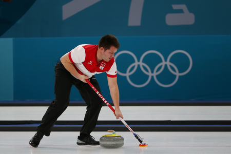 GANGNEUNG, SOUTH KOREA - FEBRUARY 10, 2018: Silver Medalist Martin Rios of Switzerland competes in the Mixed Doubles Round Robin curling match at the 2018 Winter Olympics Editorial