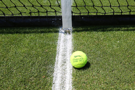 NEW YORK - JUNE 26, 2018: Slazenger Wimbledon Tennis Ball on grass tennis court. Slazenger Wimbledon Tennis Ball exclusively used and endorsed by The Championships, Wimbledon