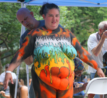 NEW YORK - JULY 14, 2018: Artists paint fully models of all shapes and sizes during 5th NYC Body Painting Day featuring artist Andy Golub on Washington Square in New York