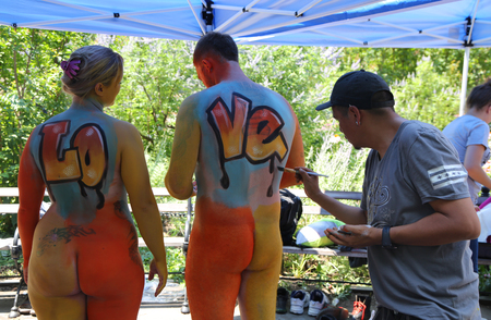 NEW YORK - JULY 14, 2018: Artists paint  fully nude models of all shapes and sizes during 5th NYC Body Painting Day featuring artist Andy Golub on Washington Square in New York