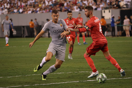 EAST RUTHERFORD, NJ - AUGUST 7, 2018: Edin Dzeko of Roma (L) and Sergio Ramos of Real Madrid #4 in action during the 2018 International Champions Cup match Real Madrid vs Roma at MetLife stadium. Editorial