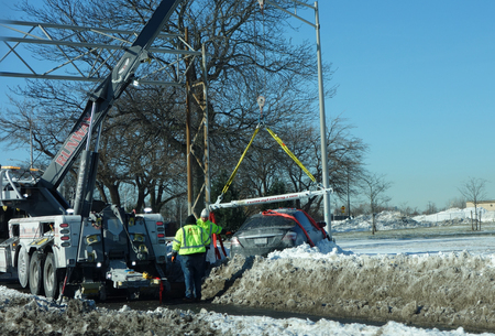 BROOKLYN, NEW YORK - JANUARY 7, 2018:Tow truck and crane  remove car  left under snow near Belt Parkway in Brooklyn after massive snowfall