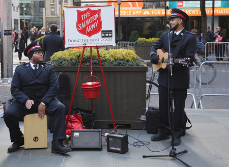 NEW YORK - NOVEMBER 29, 2018: Salvation Army soldier performs for collections in midtown Manhattan. This Christian organization is known for its charity work, operating in 126 countries