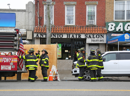 BROOKLYN, NY - APRIL 18, 2019: FDNY Engine and firefighters in front of burnt businesses after 5-alarm fire burns businesses in Brooklyn, New York. 198 Firefighters Battle 5-Alarm Fire April 17, 2019