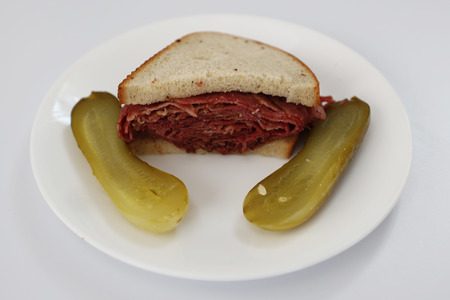 Famous Pastrami on rye sandwich served with pickles in New York Deli 스톡 콘텐츠 - 122102490