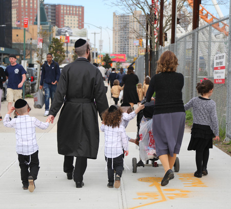 BROOKLYN, NEW YORK - APRIL 23, 2019: Jewish orthodox family enjoy outdoors during Passover at Coney Island in Brooklyn, New York Banco de Imagens - 122072528