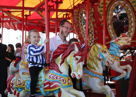 BROOKLYN, NEW YORK - APRIL 23, 2019: Jewish orthodox family ride Coney Island carousel in Luna Park during Passover at Coney Island Boardwalk in Brooklyn