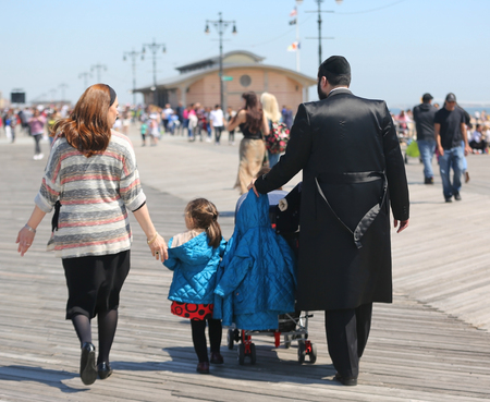 BROOKLYN, NEW YORK - APRIL 23, 2019: Jewish orthodox family enjoy outdoors during Passover at Coney Island in Brooklyn, New York Banco de Imagens - 122072532