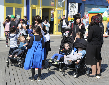BROOKLYN, NEW YORK - APRIL 23, 2019: Jewish orthodox family enjoy outdoors during Passover at Coney Island in Brooklyn, New York Banco de Imagens - 122072549