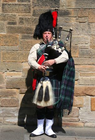 EDINBURGH, SCOTLAND - JULY 7, 2018: Scottish bagpiper on a street in Edinburgh, Scotland