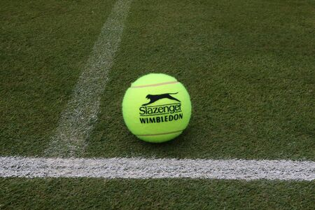 NEW YORK - JULY 2, 2019: Slazenger Wimbledon Tennis Ball on grass tennis court. Slazenger Wimbledon Tennis Ball exclusively used and endorsed by The Championships, Wimbledon