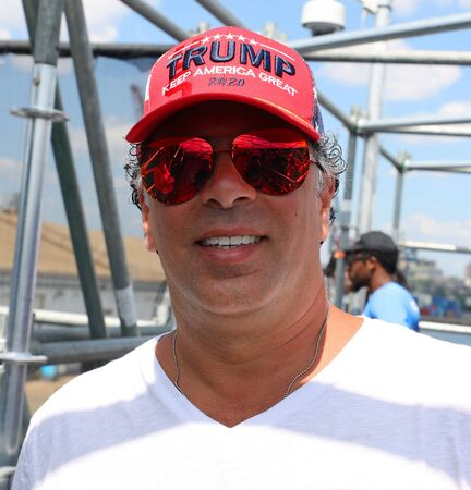 BROOKLYN, NEW YORK - JULY 14, 2019: President Donal Trump supporter wears famous red hat with sign Trump Keep America Great 2020 in Brooklyn, New York Editorial