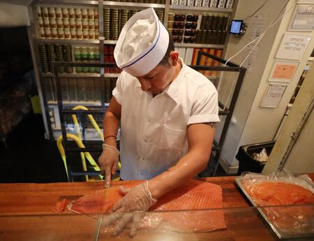 NEW YORK - JULY 30, 2019: Lox slicer at the Famous Russ & Daughters cafe in Lower East Side in Manhattan Redactioneel