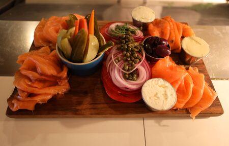Tabla de variedades de salmón ahumado con queso crema, tomate, cebolla, alcaparras y encurtidos