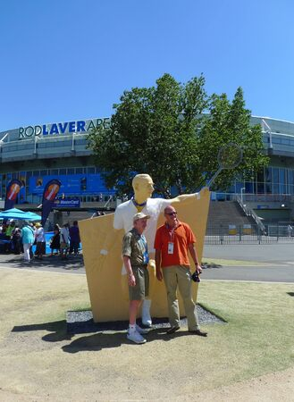 MELBOURNE, AUSTRALIA - JANUARY 29, 2009: Rod Laver posing for picture with tennis fan in front of his statue at Australian tennis center in Melbourne, Australia. Editorial