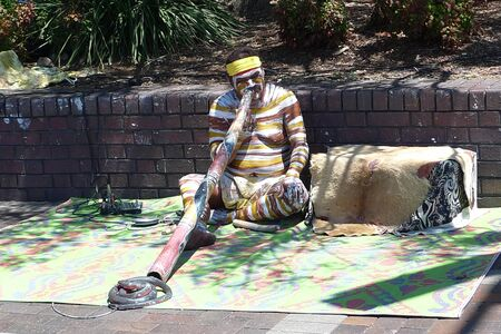 SYDNEY, AUSTRALIA - FEBRUARY 3, 2009: Unidentified body painted Aborigine playing his traditional didgeridoo
