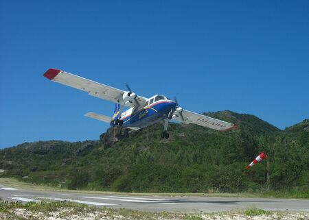 ST. BARTS, FRENCH WEST INDIES - JANUARY 24, 2008: Winair plane taking off from St Barts airport. St. Barts is considered a playground of the rich and famous