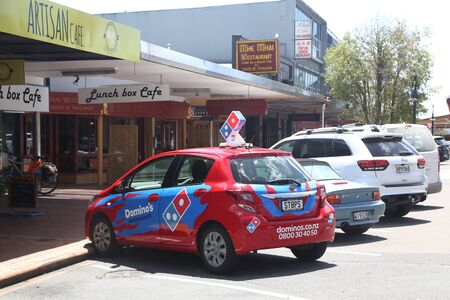 ROTORUA, NEW ZEALAND - FEBRUARY 2, 2019: Domino Pizza delivery car at the popular Eat Street in Rotorua, New Zealand. Eat Street is one of Rotoruas coolest hot spots in the city. Sajtókép