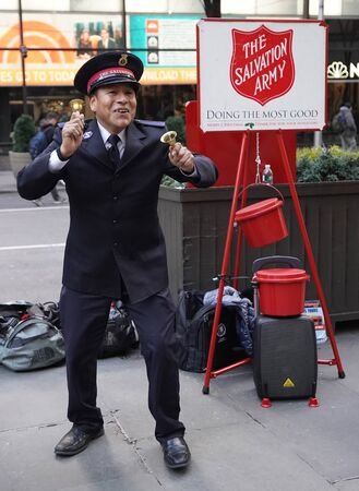 NEW YORK - DECEMBER 5, 2019: Salvation Army soldier performs for collections in midtown Manhattan during holidays season. This Christian organization is known for its charity work, operating in 126 countries Editorial