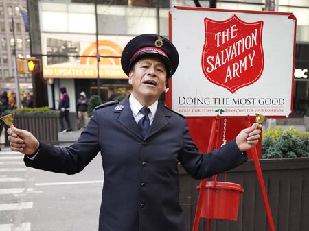 NEW YORK - DECEMBER 5, 2019: Salvation Army soldier performs for collections in midtown Manhattan during holidays season. This Christian organization is known for its charity work, operating in 126 countries