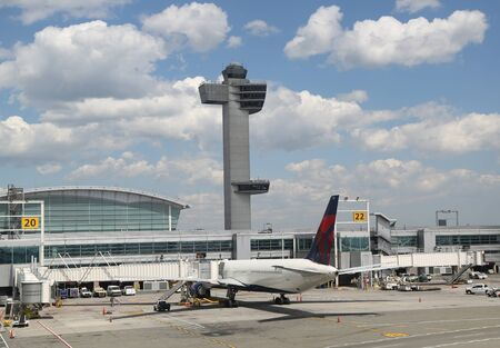NEW YORK - May 16, 2019: Air Traffic Control Tower and Delta Airlines plane on tarmac at Terminal 4 at JFK International Airport. JFK is one of the biggest airports in the world with 4 runways and 8 terminals