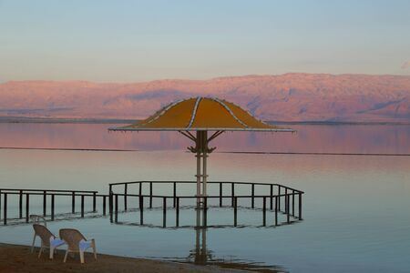 Gazebo for sun protection reflected in Dead Sea water at sunset