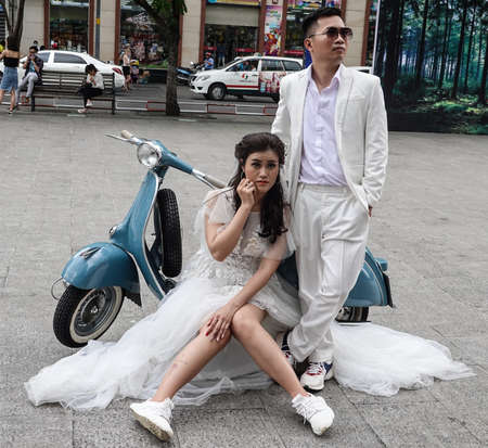 HO CHI MINH, VIETNAM - NOVEMBER 3, 2019: Bride and groom taking pictures on scooter before wedding at Nguyen Hue walking street in Ho Chi Minh, Vietnam