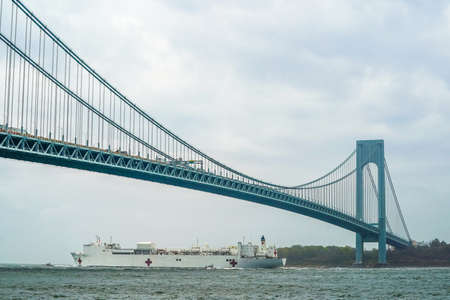 NEW YORK - APRIL 30, 2020:  The USNS Comfort Hospital Ship leaves New York Harbor and sails under the Verrazzano-Narrows Bridge after a month of caring for patients with the Coronavirus