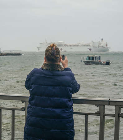 NEW YORK - APRIL 30, 2020: Spectators on the Brooklyn shoreline take pictures as the USNS Comfort Hospital Ship departing New York City after a month of caring for patients with the Coronavirus