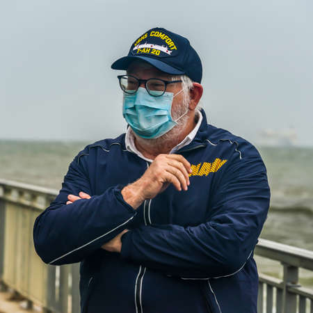 NEW YORK - APRIL 30, 2020:United States Navy veteran on the Brooklyn shoreline as the USNS Comfort Hospital Ship departing New York City after a month of caring for patients with the Coronavirus. Sajtókép