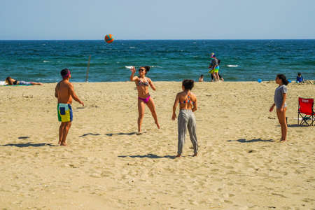 FAR ROCKAWAY, NEW YORK - MAY 15, 2020: Sunbathers and swimmers fill the beach at Rockaway Beach in Jacob Riis Park during COVID-19 pandemic. New York City beaches are currently closed for swimming Редакционное