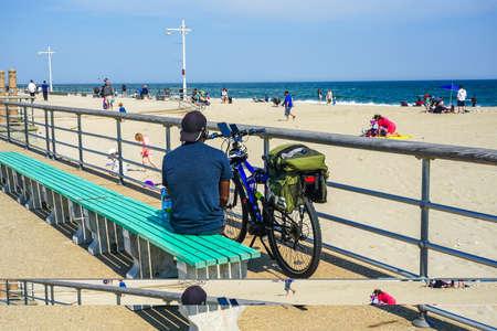 FAR ROCKAWAY, NEW YORK - MAY 15, 2020: Bicyclists enjoy outdoor during COVID-19 pandemic at the Riis Park boardwalk in Far Rockaway, New York