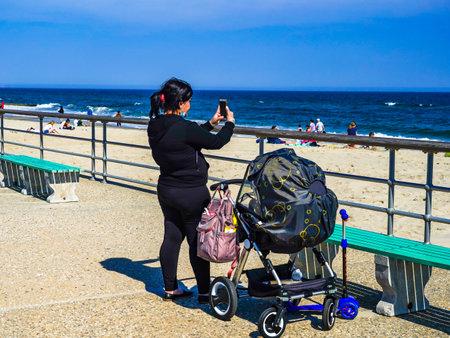 FAR ROCKAWAY, NEW YORK - MAY 15, 2020: Pedestrians enjoy outdoor during COVID-19 pandemic at the Riis Park boardwalk in Far Rockaway, New York Редакционное